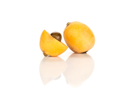 One fresh orange Japanese loquat one half with a seed isolated on white background  Imagens