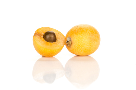 One fresh orange Japanese loquat and sliced half with a seed inside isolated on white background