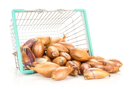 Golden shallots out a shopping basket isolated on white background