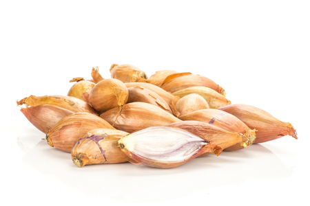 Golden shallots stack and one sliced half isolated on white background  写真素材