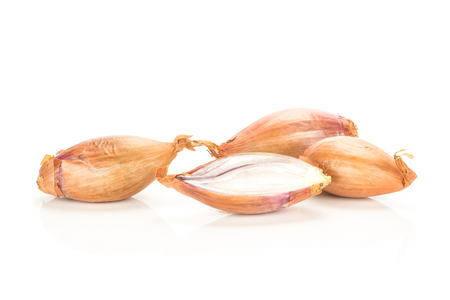 Three unpeeled shallots with one section half isolated on white background