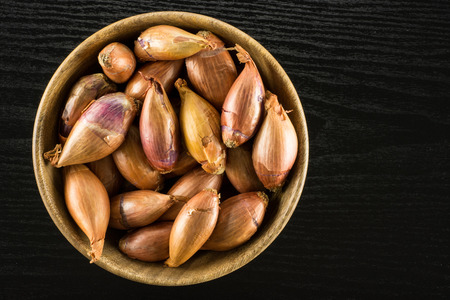 Long shallot in a wooden bowl top view isolated on black wood background
