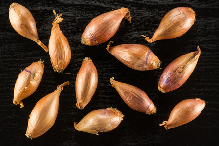 Long golden shallots top view isolated on black wood background  写真素材
