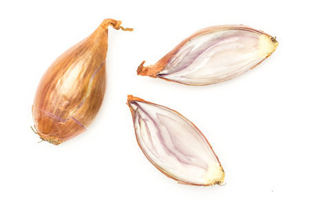 One unpeeled shallot and two sliced halves flatlay isolated on white background