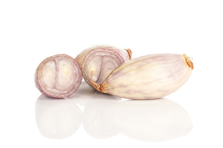 Peeled shallot one whole and two halves isolated on white background  写真素材