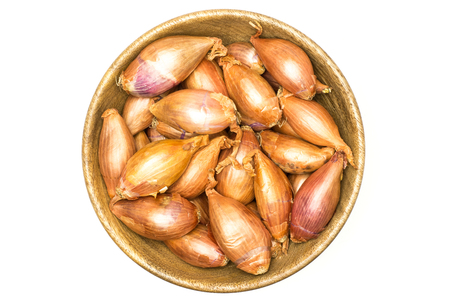 Long shallot in a wooden bowl top view isolated on white background