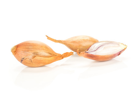 Two unpeeled shallots with one half isolated on white background