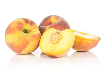 Two yellow peaches with one cut in half isolated on white background 免版税图像
