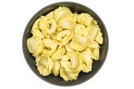 Raw tortellini pasta in a grey ceramic bowl flatlay isolated on white background Italian traditional dumpling