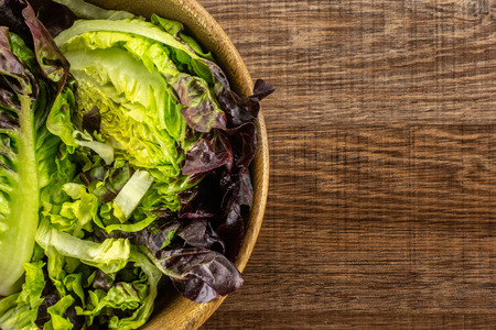 Fresh green lettuce red little gem variety chopped in a wooden bowl flatlay on brown wood
