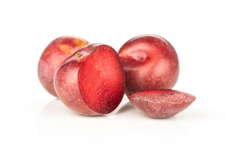 Group of two whole two halves of fresh pluot interspecific plums variety one sliced isolated on white