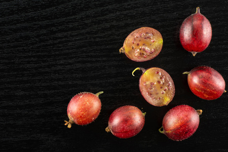 Group of five whole two halves of fresh red gooseberry hinnomaki variety flatlay on black wood