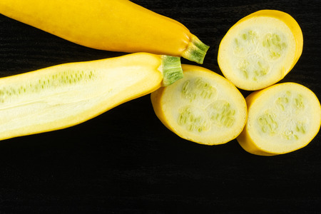 Group of one whole one half three slices of raw yellow zucchini flatlay on black wood Stock Photo