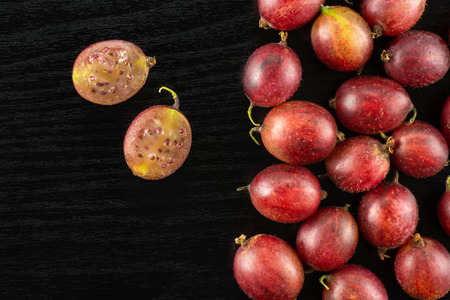 Lot of whole fresh red gooseberry hinnomaki variety one cut in two section halves flatlay on black wood