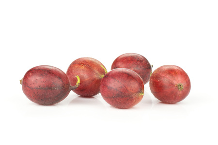 Group of five whole fresh red gooseberry hinnomaki variety stack isolated on white Stock fotó