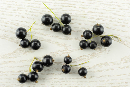 Lot of whole fresh black currant berry ben gairn variety five strigs flatlay on grey wood