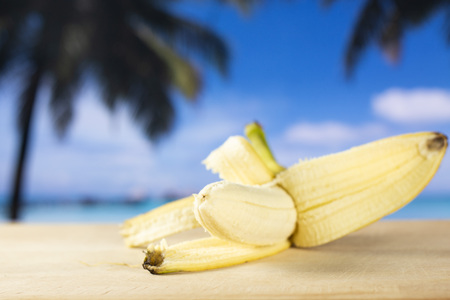 One whole fresh yellow banana opened like a plane with palm trees on the beach in background Stock fotó