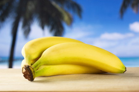 Group of four whole fresh yellow banana one ripe cluster with palm trees on the beach in background
