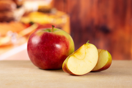 Group of one whole two slices of fresh red apple james grieve variety with rustic wood kitchen in background Stock fotó