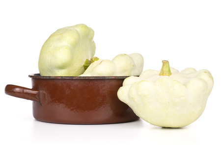 Group of three whole summer white pattypan squash in a brown cast iron pan isolated on white background 版權商用圖片