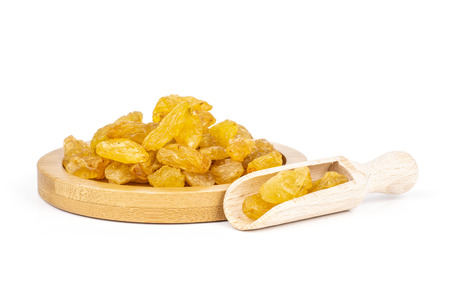 Lot of whole dry golden raisins sultana variety on bamboo plate isolated on white background Archivio Fotografico