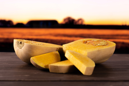 Group of two halves three slices of smooth pear shaped orange butternut squash waltham variety with autumn field and sunset in background Stock Photo