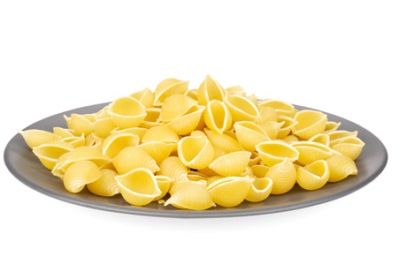 Lot of whole raw yellow pasta conchiglie variety on grey ceramic plate isolated on white background