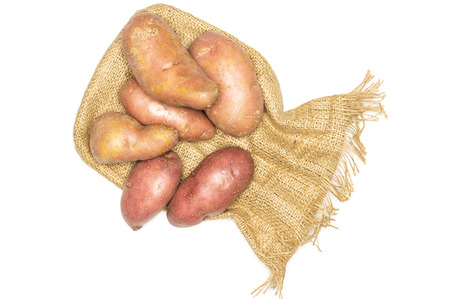 Group of six whole raw fresh red potato francelina variety on jute cloth flatlay isolated on white background