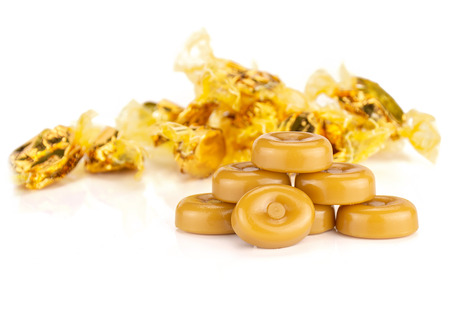 Group of seven whole caramel cream candy butterscotch variety with yellow gliser covered bonbons isolated on white background Stock Photo