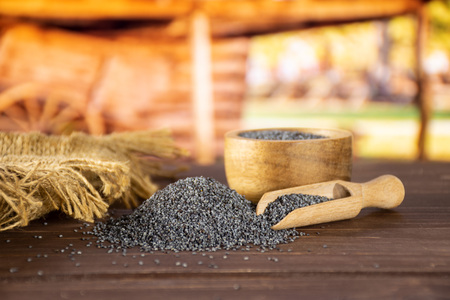 Lot of whole czech blue poppy seeds in a bowl with wooden scoop with cart in background Banque d'images