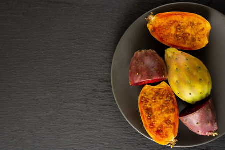 Group of one whole four halves of fresh bright prickly pear opuntia on grey ceramic plate flatlay on grey stone