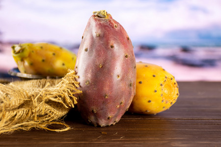 Group of three whole fresh bright prickly pear opuntia on jute cloth with desert in background