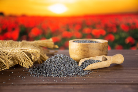 Lot of whole czech blue poppy seeds in a bowl with wooden scoop with red poppy flowers in background Banque d'images