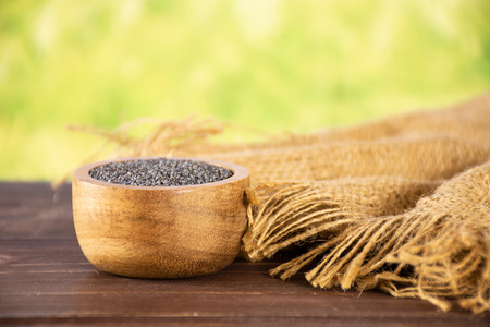 Lot of whole czech blue poppy seeds jute cloth with wooden bowl with green wheat field in background