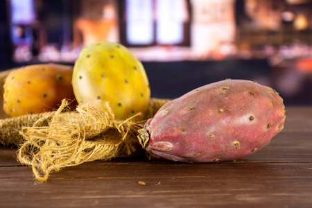 Group of three whole fresh bright prickly pear opuntia on jute cloth with restaurant in background
