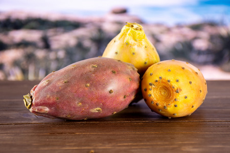 Group of three whole fresh bright prickly pear opuntia with desert in background Stock Photo