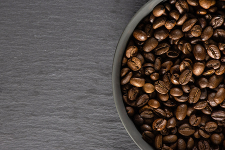 Closeup of lot of whole dark brown coffee beans sweet arabica variety in a grey ceramic bowl flatlay on grey stone