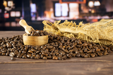 Lot of whole dark brown coffee beans sweet arabica variety in a light scoop with wooden bowl with restaurant in background