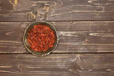 Lot of whole dried red goji berries in old iron bowl flatlay on brown wood