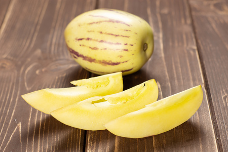 Group of one whole three slices of fresh striped pepino melon on brown wood