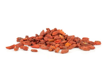 Lot of whole dried red goji berries heap isolated on white background