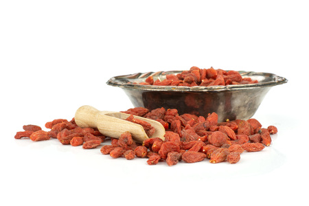 Set of lot of whole dried red goji berries in old iron bowl isolated on white background