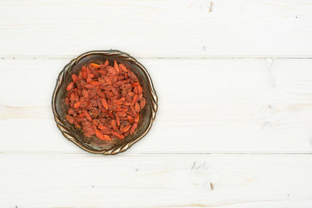 Lot of whole dried red goji berries in old iron bowl flatlay on white wood