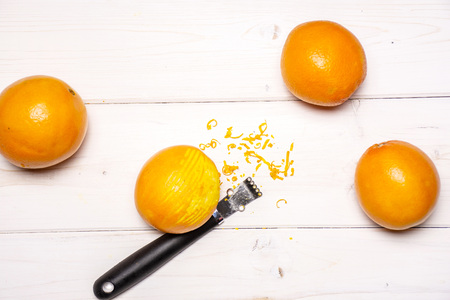Scraping orange zest with a peeler. recipe step by step hot red mulled wine flatlay on white wood