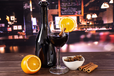 Glass of hot wine with oranges and a bottle, ready to drink. recipe step by step hot red mulled wine with restaurant in background Standard-Bild