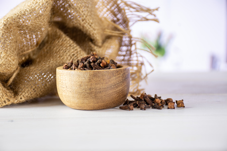 Lot of whole small dried cloves spice scoop and textil with wooden bowl with red flowers on white in background