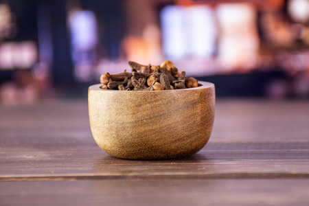Lot of whole small dried cloves spice with wooden bowl with restaurant in background