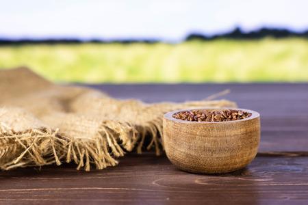 Beaucoup de tissu de jute de riz rouge cru entier avec bol en bois avec champ de blé vert en arrière-plan Banque d'images