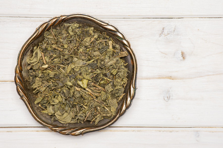 Lot of pieces of dry green tea with copyspace in old iron bowl flatlay on white wood 版權商用圖片