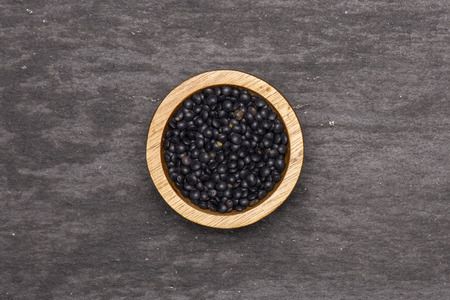 Lot of whole black lentils beluga variety with wooden bowl flatlay on grey stone